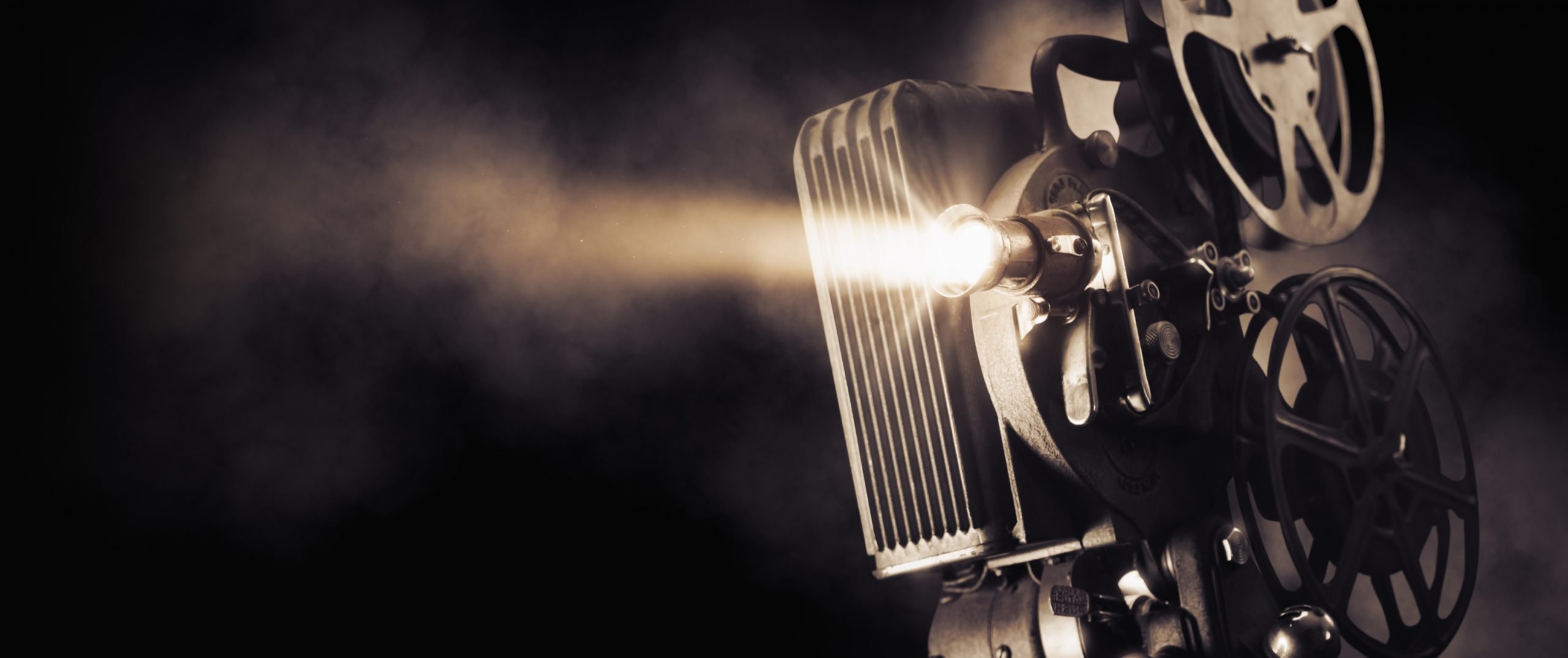 Movie projector on a dark background with light beam